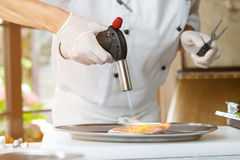 Man's hand with torch burner. Torch blowing fire on meat. Chef is preparing duck breast. Be careful not to overcook stock photos
