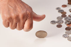 Man's hand tossing coin closeup. With coins on the right on white background Stock Image