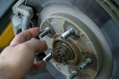 Man`s hand touches the bolts of the car caliper royalty free stock images