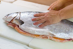 Man's hand touches raw fish. Knife cuts big fish. Fresh salmon on cooking board. Quality product from the supermarket Stock Photos
