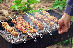 Mans hand turn over kebabs on a barbecue Royalty Free Stock Images