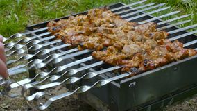 Man`s hand turn over shashlik or barbecue on a grill.  stock video footage
