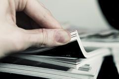 Man's hand turned over a stack of magazines Royalty Free Stock Images