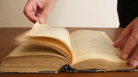 A man's hand turning on pages on some book. stock footage