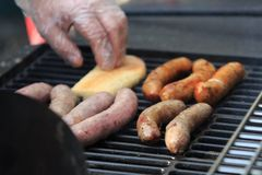 The man`s hand turns the delicious sausage which is roasting on a grill Stock Image