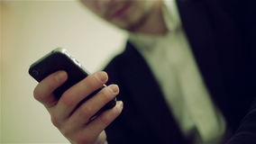 Man's hand is typing on mobile phone. White shirt and black jacket are behind the hand with mobile stock video