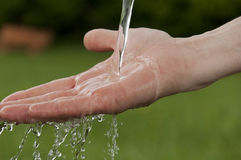 Man's hand under running water Stock Photo