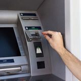 Man's hand using the ATM Stock Photos