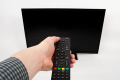 Man`s hand using remote control in front of the TV. A Man`s hand using remote control in front of the TV Royalty Free Stock Photos