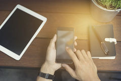 man's hand using smartphone with digital tablet Stock Images