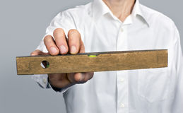 Man's hand with vintage carpenter's leveler Royalty Free Stock Image