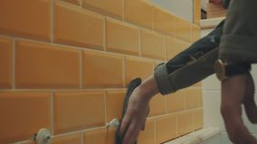 Man`s hand washed away the remnants of putty from orange tiles on the wall stock footage