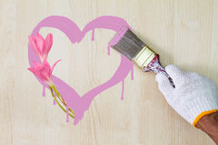 Man`s hand wearing white glove holding old grunge paintbrush and painting pink heart on wooden wall with pink flowers. Valentine love concept Stock Images