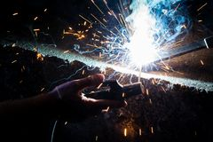 Man`s hand welding steel with sparks royalty free stock images