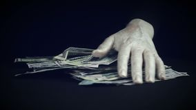 Manipulations with a pack of money. A man`s hand in white makeup makes magical movements over a wad of money. Hand throws dollars on the table and puts a fan