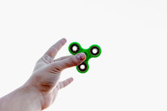 Man`s hand who is holding green fidget spinner Stock Photos