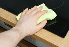 Man's hand wipes cooktop. Stock Photo
