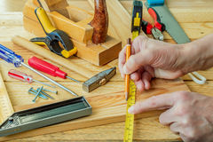 Man`s hand working on carpenter`s desk and working tools Stock Image