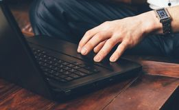 A man`s hand with a wrist watch stands on the laptop`s touchpad. Businessman works at home in his own room stock image