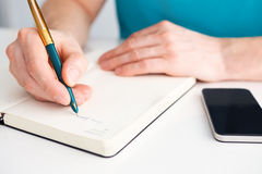 Man's hand writes a pen on diary Stock Photos