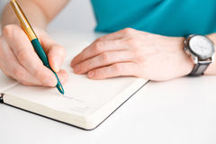 Man's hand writes a pen on diary Royalty Free Stock Images