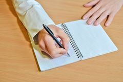 A man`s hand writes the text with a black pen in a notebook with a spiral on a wooden table, holding the sheet with hand royalty free stock photos