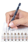Man's hand writing on a book Royalty Free Stock Image