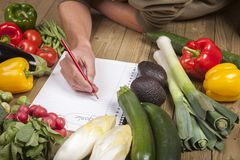 Man's hand writing list of organic vegetables Royalty Free Stock Photos