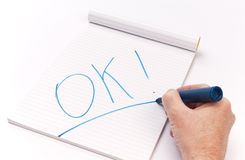 Man's hand writing ok on a block notes Royalty Free Stock Image