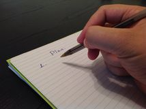 Man's hand writing plan title on a paper sheet Royalty Free Stock Photo