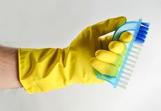 A man& x27;s hand in a yellow latex glove holds a plastic brush on a white background. Cleaning concept. stock images