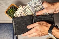 Man& x27; s handen die het zwarte hoogtepunt van de leerportefeuille van dollarrekeningen houden Stock Foto