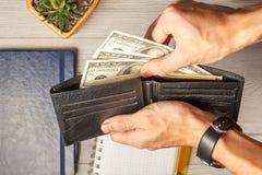 Man& x27; s handen die het zwarte hoogtepunt van de leerportefeuille van dollarrekeningen houden Stock Fotografie