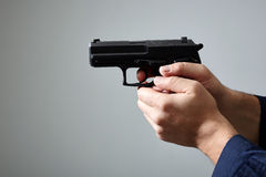 Man`s hands aiming with gun. Closeup view of man`s hands aiming with gun Stock Photos
