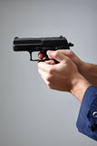 Man`s hands aiming with gun. Closeup view of man`s hands aiming with gun Stock Photo
