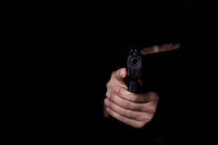 Man`s hands aiming with gun. Closeup view of man`s hands aiming with gun Stock Photography