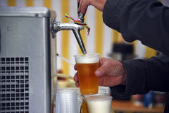 Man& x27;s hands at a beer tap pouring beer in plastic glasses in a m Royalty Free Stock Images