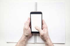 Man's hands with blank smartphone and diary, mock up Royalty Free Stock Photo