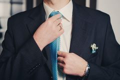 Man's hands closeup tying his tie knot stock images