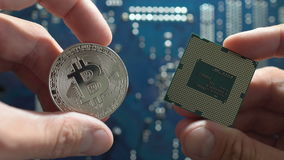 Man`s hands compare silver`s Bitcoin and cpu on motherboard background. Man hands compare silvers Bitcoin and cpu on motherboard background. new metal stock footage