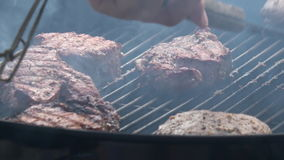 Man`s hands cooking steak on grill stock footage
