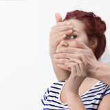 Man's hands covering caucasian redhair woman's mouth and one eye Stock Photography