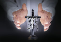Man's hands with crucifix and a black rosary Stock Images