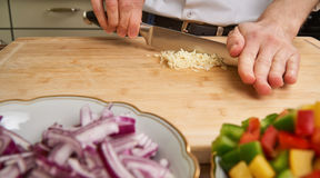 Man`s hands cutting fresh garlic in the kitchen, preparing a meal for lunch. Paprika and onions in the foreground. stock images