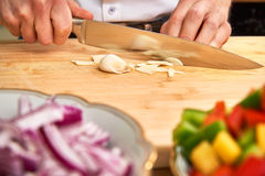 Man`s hands cutting fresh garlic in the kitchen, preparing a meal for lunch. Paprika and onions in the foreground. Stock Photo