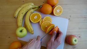 Man`s Hands Slicing Orange With Knife On Chopping Board stock video footage