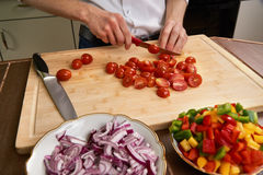 Man`s hands cutting fresh tomatos in the kitchen, preparing a meal for lunch. Frontal view. Stock Images