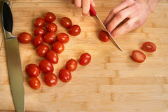 Man`s hands cutting fresh tomatos in the kitchen, preparing a meal for lunch. Topdown view. Stock Photo