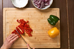 Man`s hands cutting fresh vegetables in the kitchen, preparing a meal for lunch. Top down view. Royalty Free Stock Images
