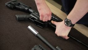 Man`s hands disassemble the rifle.  stock footage